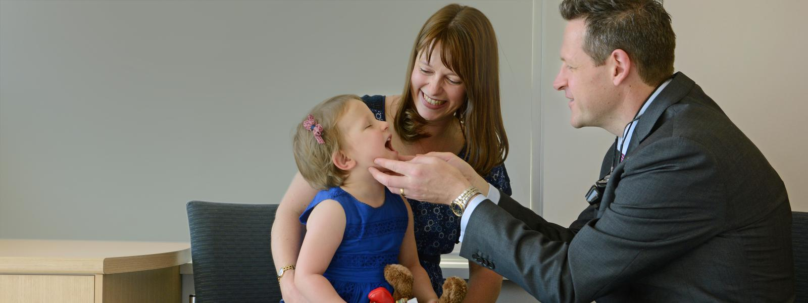 Dr with Parent and Child Patient examining throat